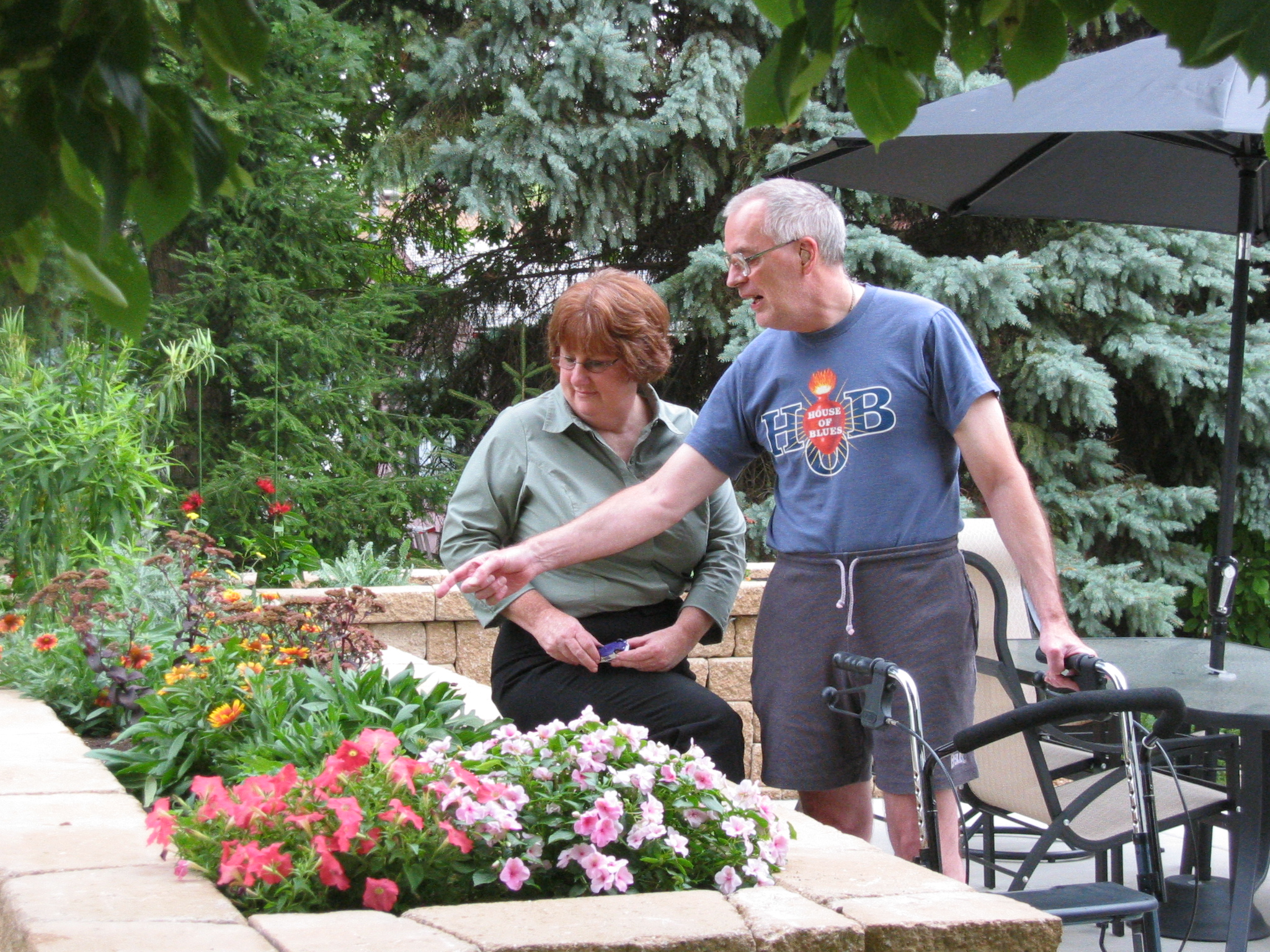 Mike and Ann enjoying their raised garden bed full of colorful flowers.