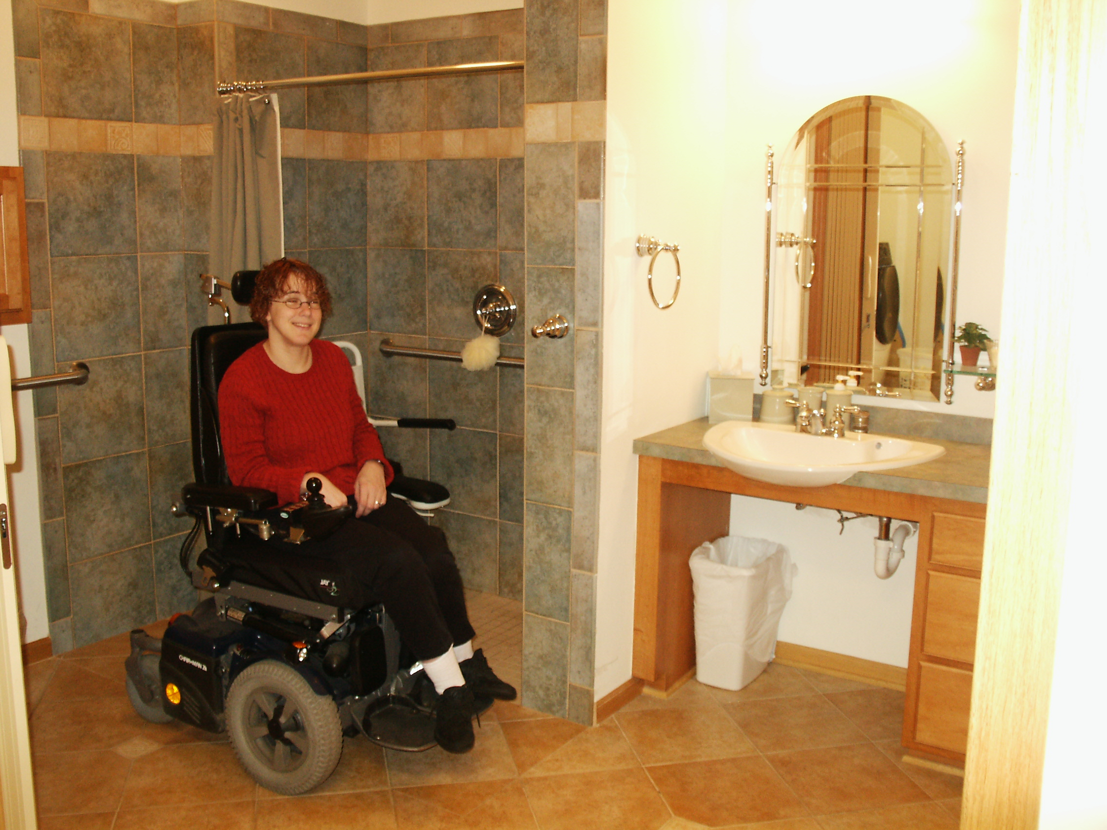 Michelle Nickerson showing off her new roll-in shower and accessible bathroom sink in while in her wheelchair.