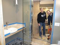 Bath Crashers host Matt Muenster and one of the contractors working in the bathroom.