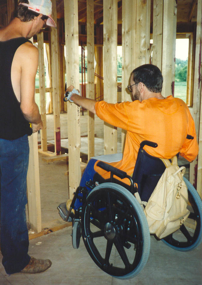 Steve verifying his reach range with the builder while he is seated in his wheelchair.
