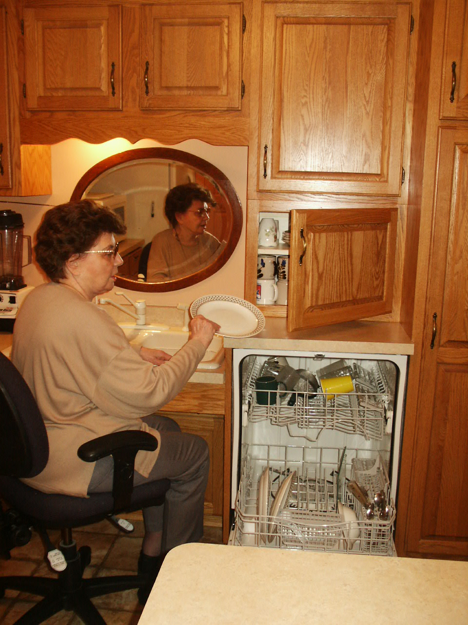 Jeanne putting dirty dishes into her dishwasher while in a seated position.