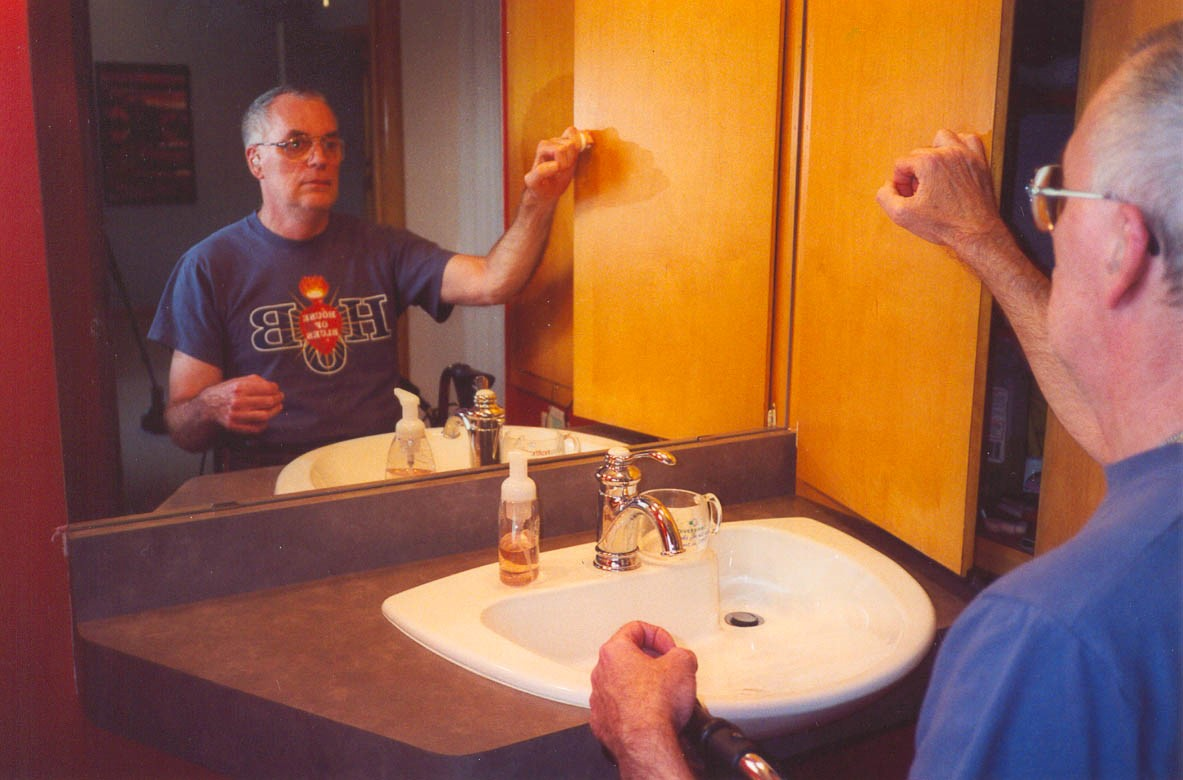 Mike seated at the bathroom vanity accessing his medicine cabinet installed within seated reach range.