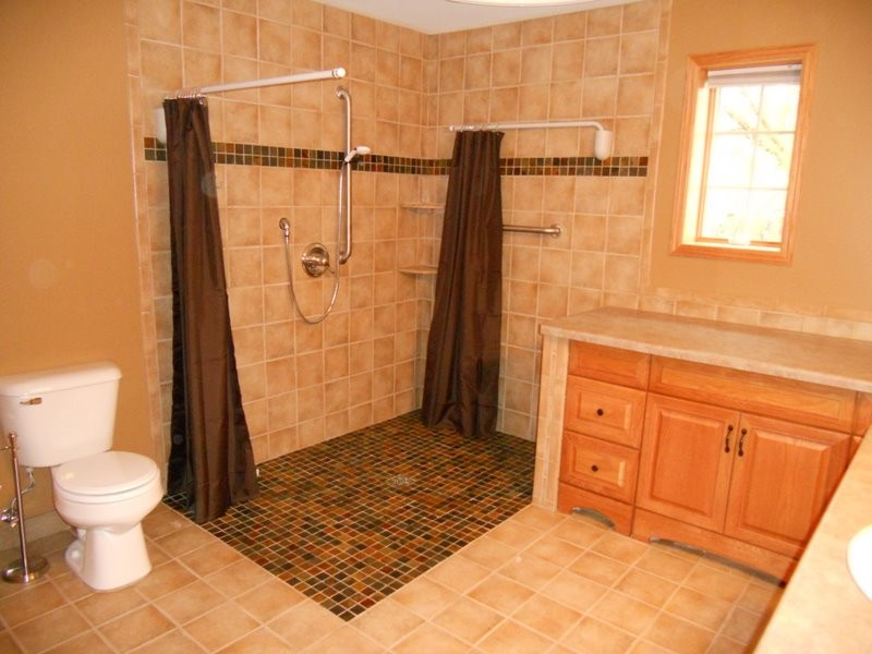 Accessible roll-in shower with swing away shower curtain poles.