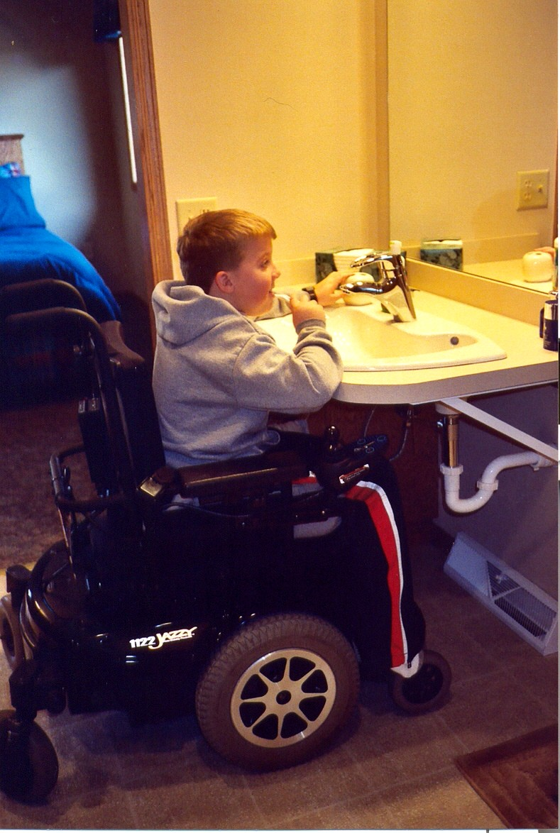 Brock seated in his wheelchair at his new accessible bathroom sink brushing his teeth.
