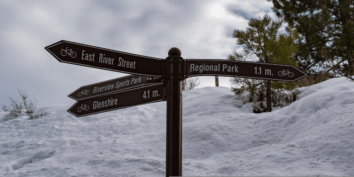 A sign at the trail junction of the Legacy Trail in Truckee. Snow in the background.