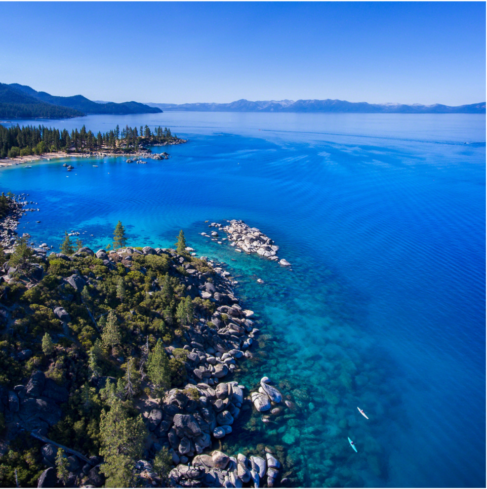 Lake Tahoe viewed from the air with paddleboarders on the blue water.