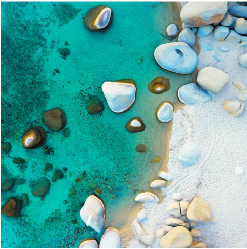 Turquoise water and white sand along the Lake Tahoe shoreline.