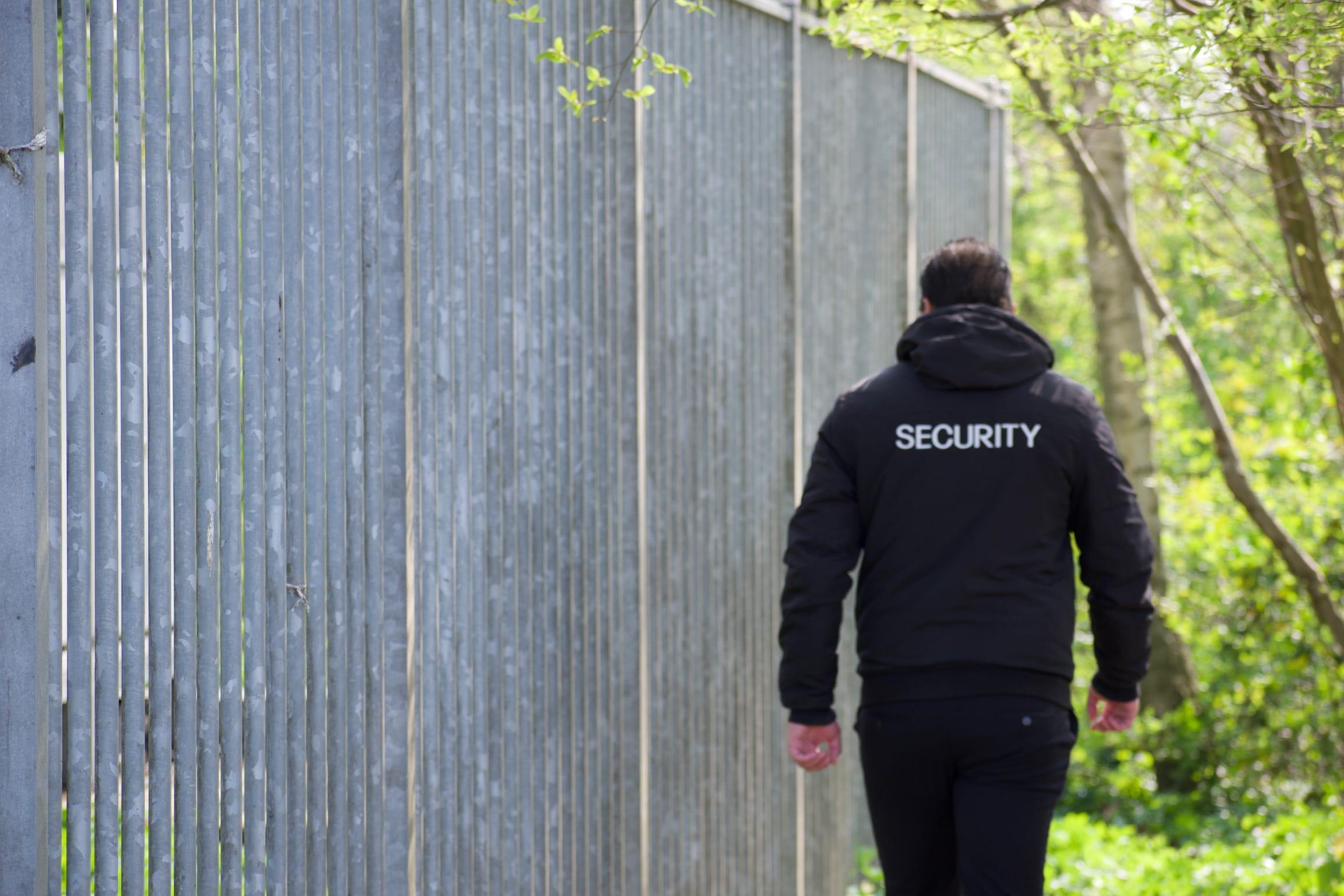 Bouw beveiliger loopt bij poort