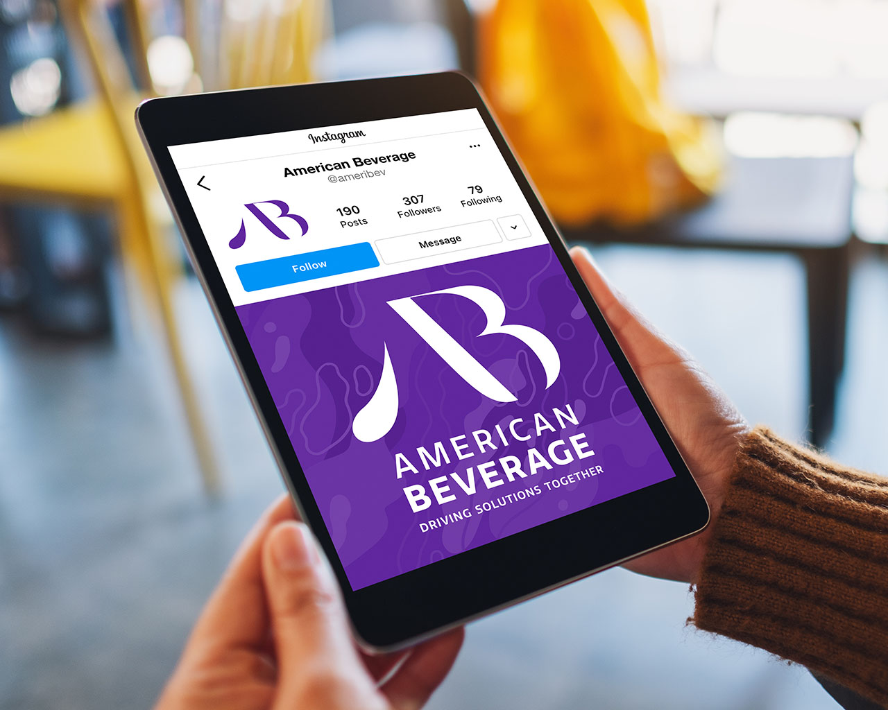 Hands holding a tablet with the American Beverage Instagram page on screen