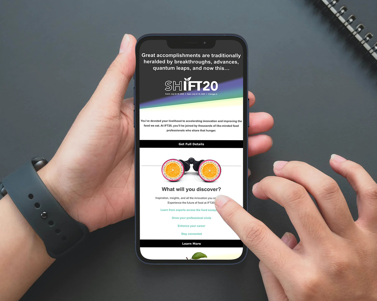 Hands holding a phone with an email promoting SHIFT 2020 on the screen