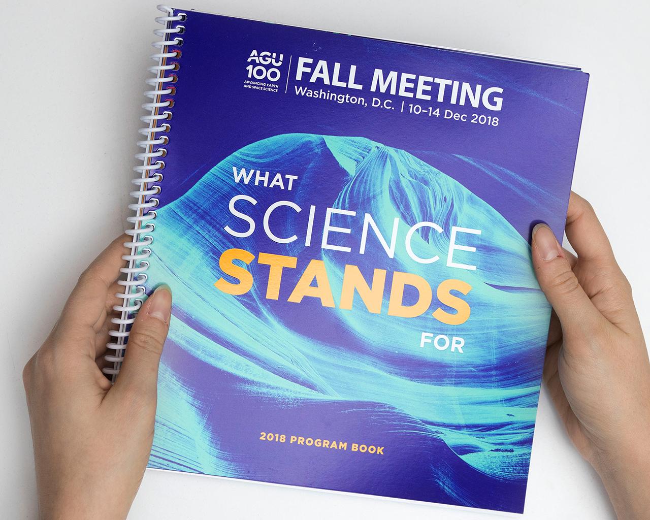 Hands holding the AGU Fall Meeting 2019 program book