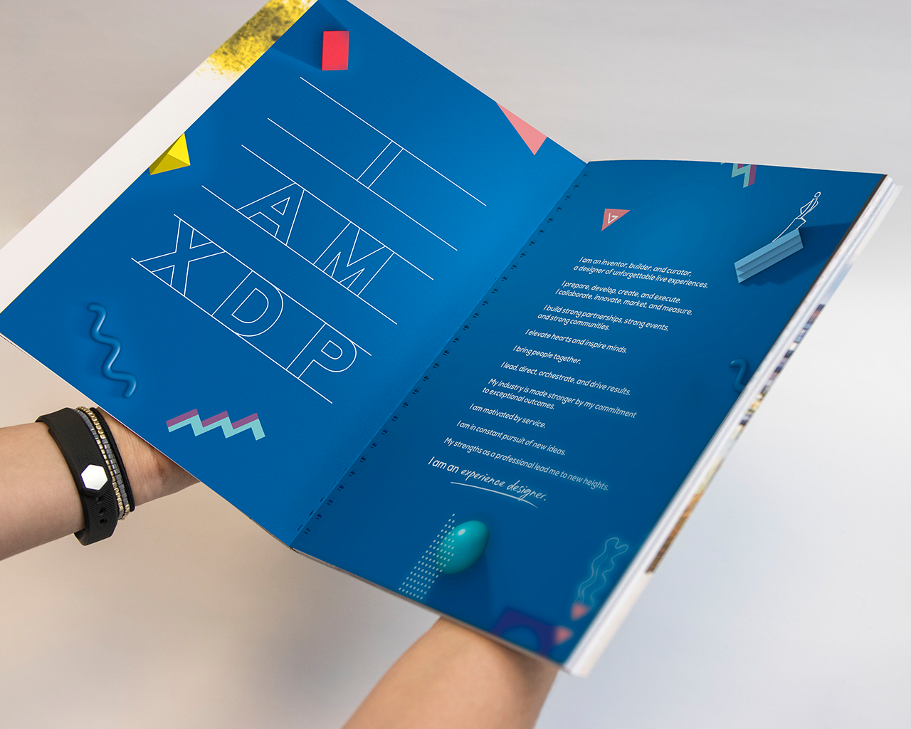 Hands holding an open spread of the XDP 2019 event playbook
