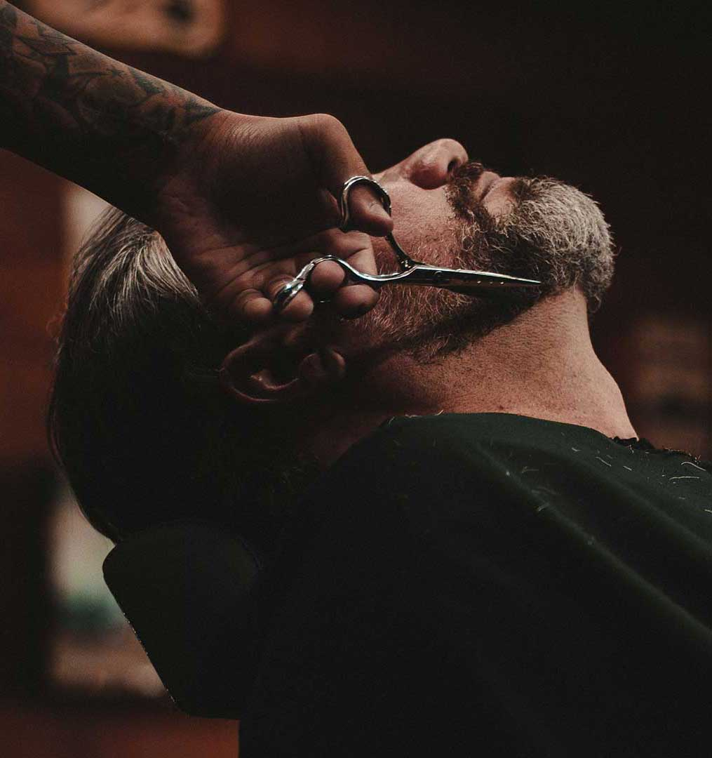A man having his beard trimmed professionally