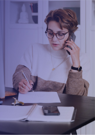 A woman with glasses working on on the phone.