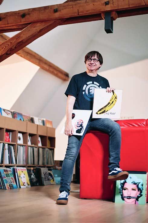 Raimund Flöck auf rotem Sofa mit zwei Plattencovern in den Händen