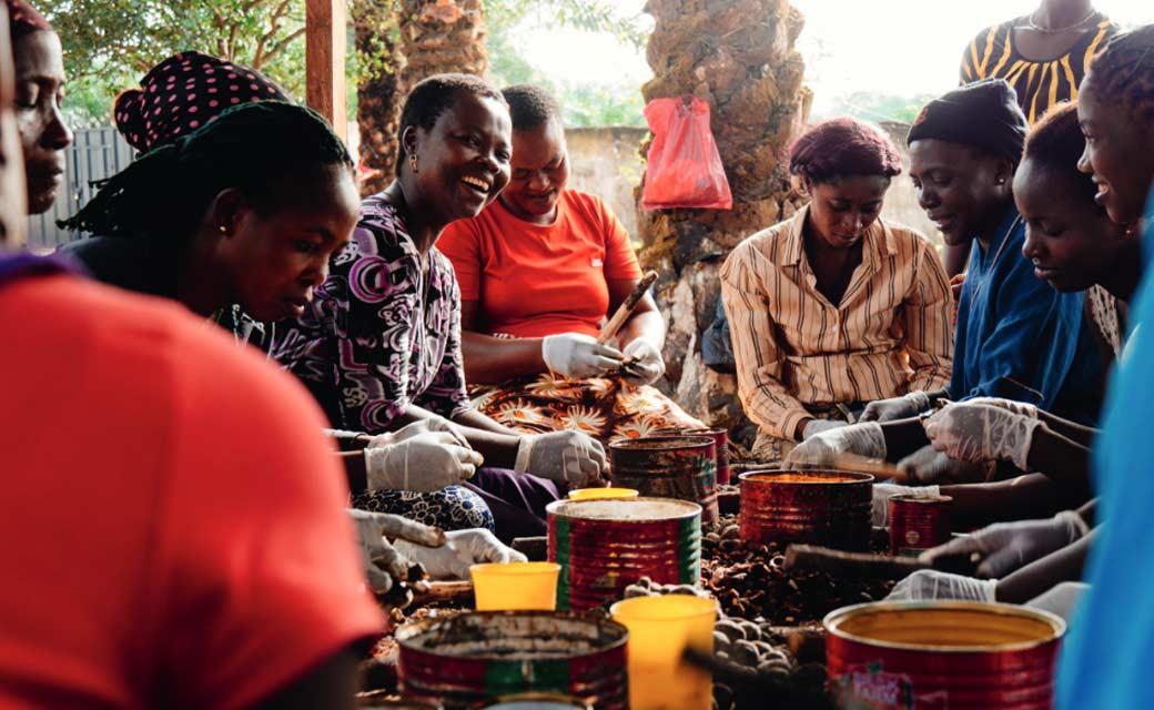 Gruppe afrikanischer, auf Boden sitzender Frauen bei der Arbeit