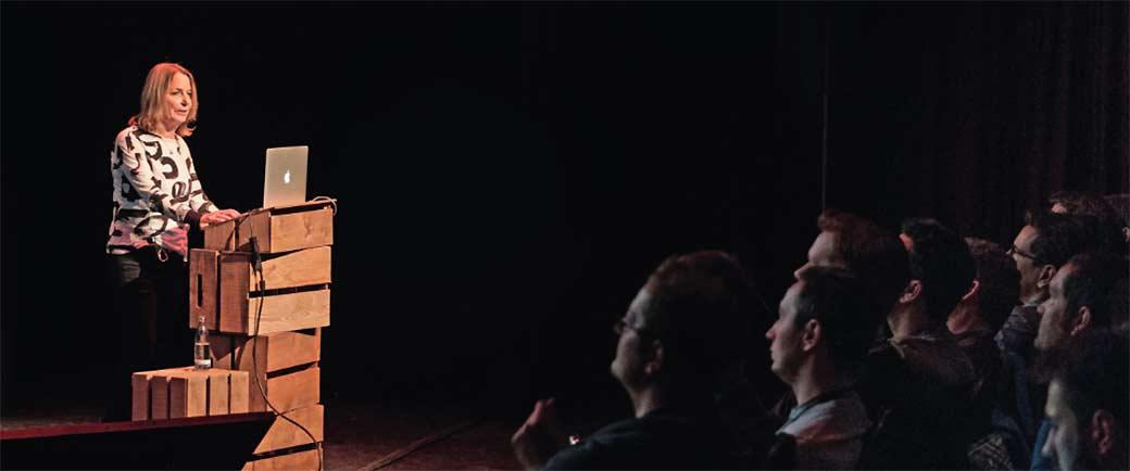 Referentin am Podium auf Bühne vor Publikum