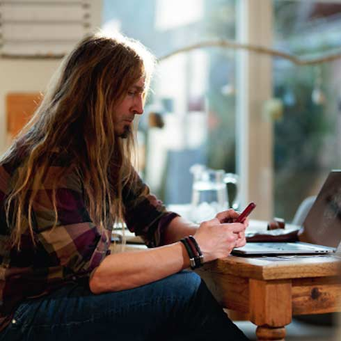 Seitenprofil von Marc Thiele mit Handy in der Hand vor Tisch