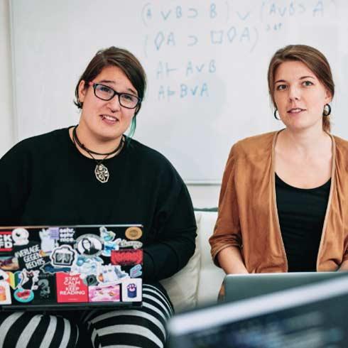 Zwei Frauen auf Sofa mit Laptop auf dem Schoß