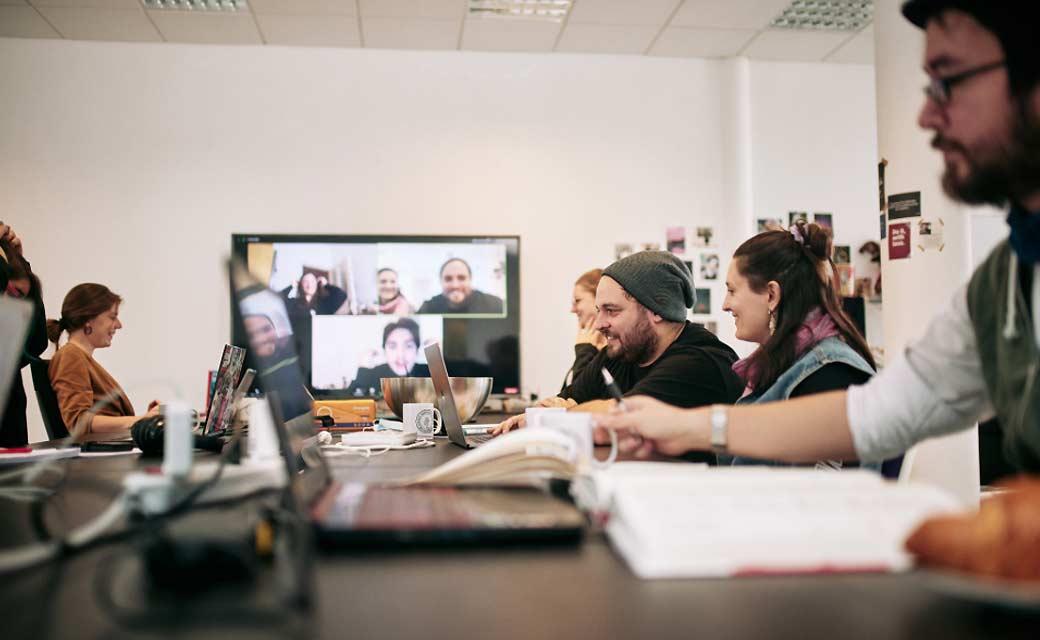 Konferenztisch mit mehrere Personen und Bildschirm am Tischende