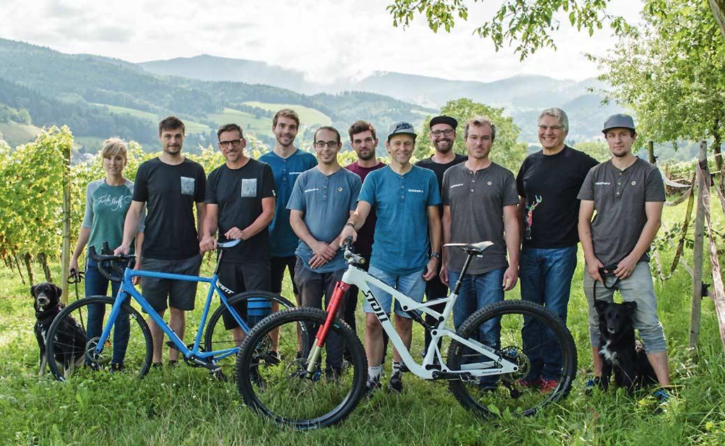 Gruppenfoto des Trickstuff-Teams im Weinberg mit Mountainbike und Rennrad