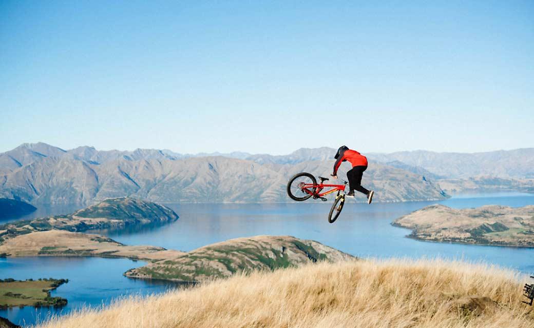 Fahrrad Trickfahrer in Aktion vor Berg- und Seekulisse