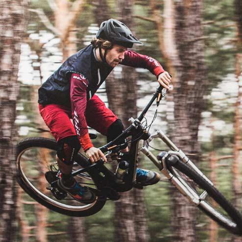 Downhiller auf Mountainbike beim Sprung in der Luft