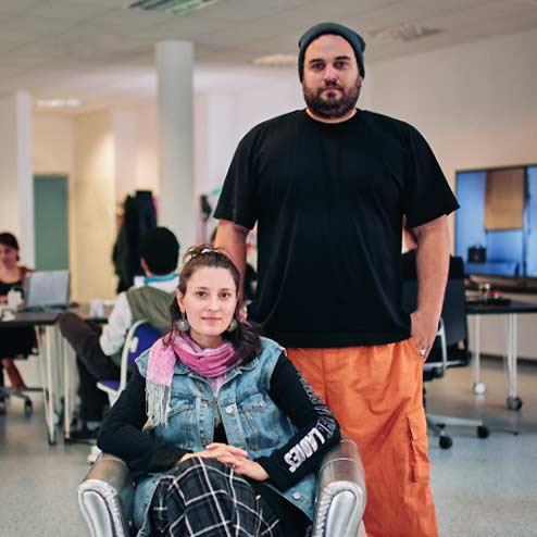Frau auf Sessel und Mann, der dahinter steht