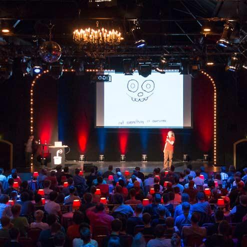 Mann auf Bühne vor Publikum