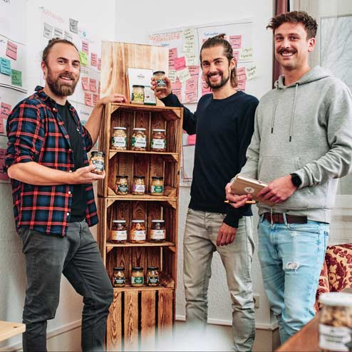 Die drei Gründer von Fairfood vor Holzregal mit Nussprodukten