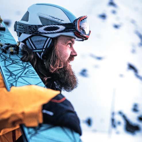 Frederic Andes mit Skihelm und Skiern über Schulter im Seitenprofil