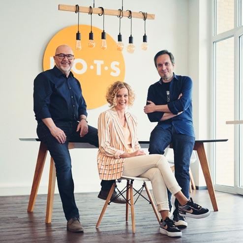 Die drei Gründer:innen der Agentur Dots am Schreibtisch