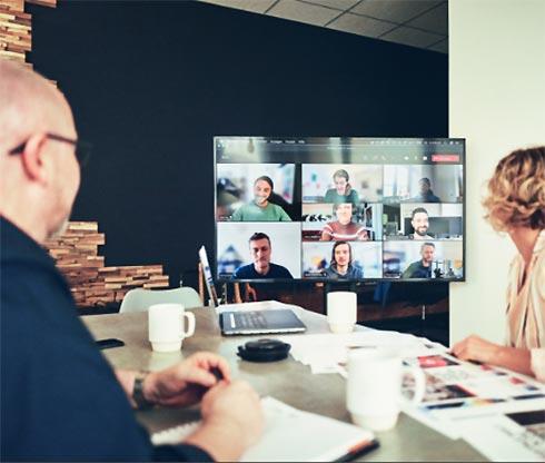 Bildschirm vor Schreibtisch mit Porträts des dots-Teams
