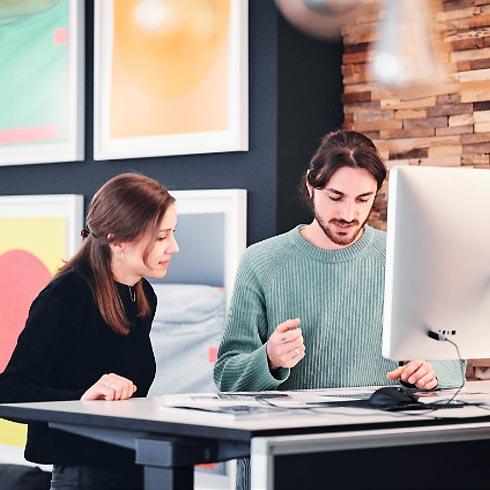 Junger Mann und junge Frau am Schreibtisch
