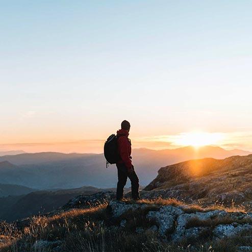 Wanderer auf Berggipfel im Sonnenuntergang