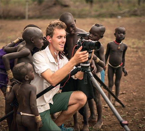 Vor Stativ hockender Fotograf in Afrika, umringt von farbigen Kindern