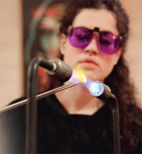 Glasbläserin mit Schutzbrille bei der Arbeit