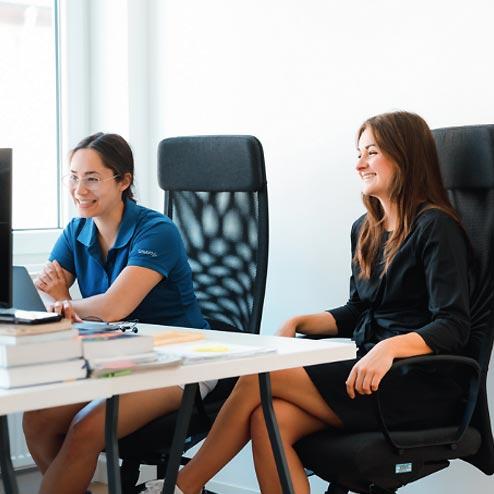 Zwei am Schreibtisch sitzende Frauen, die auf Bildschirm schauen