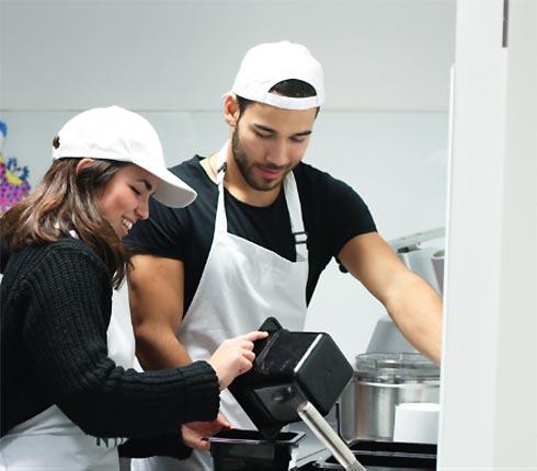Mann und Frau mit Schürze und Cap bei der Arbeit in Küche