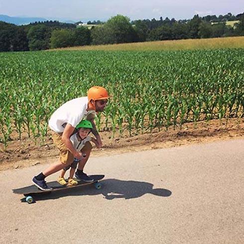 Mann mit Kind auf Longboard vor Maisfeld