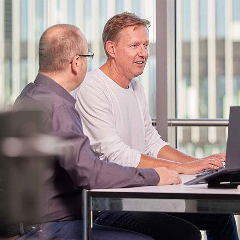 Zwei Männer am Schreibtisch vor PC