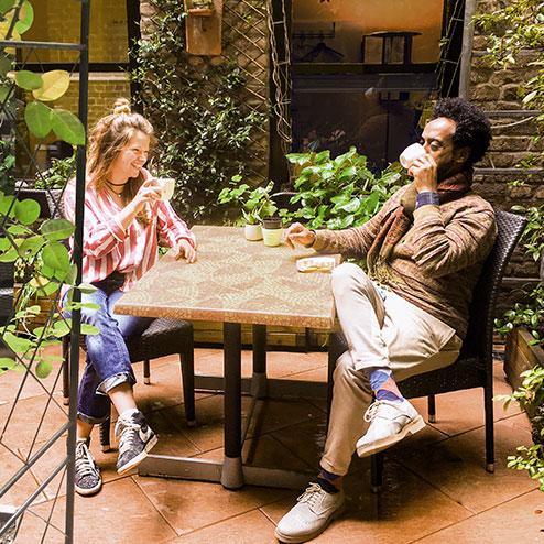 Frau und Mann trinken Kaffee im Garten