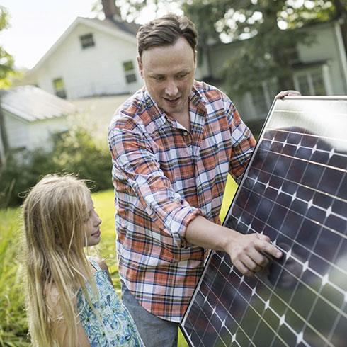 Mann zeigt Kind Solaranlage
