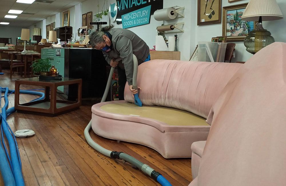 A man vacuuming upholstery.