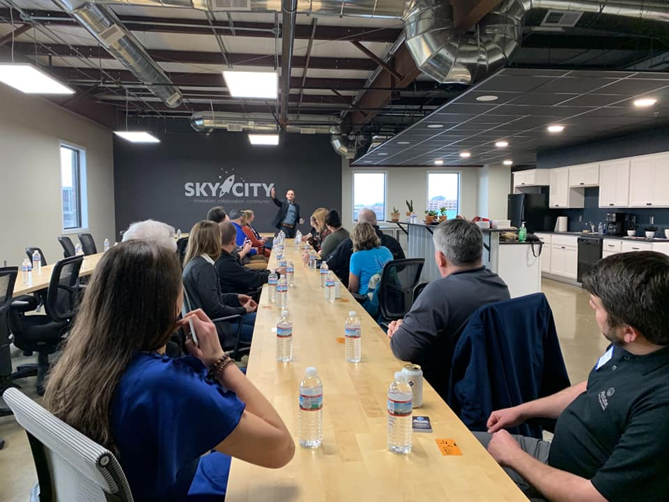 Image of a Sky City event with attendees sitting at a long conference table listening to the speaker