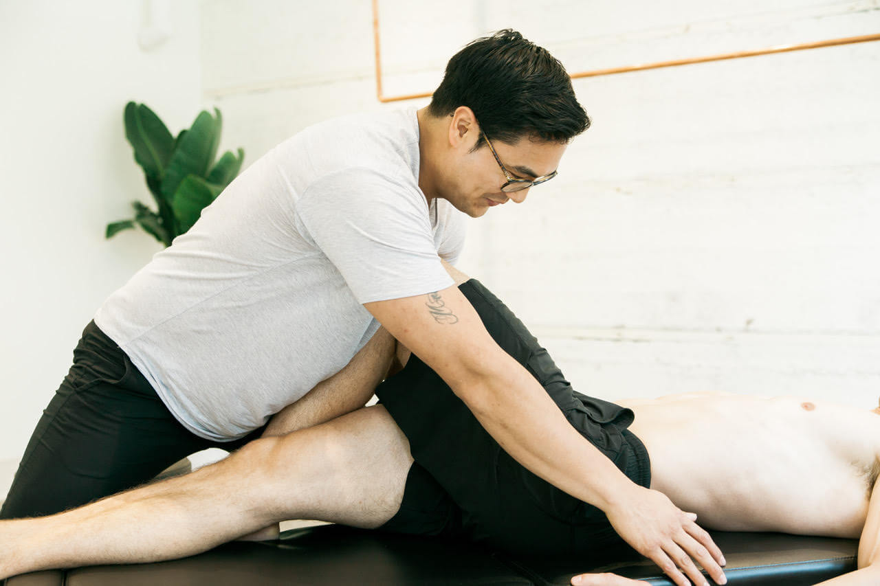 Man using massage to treat a patient's lower back pain