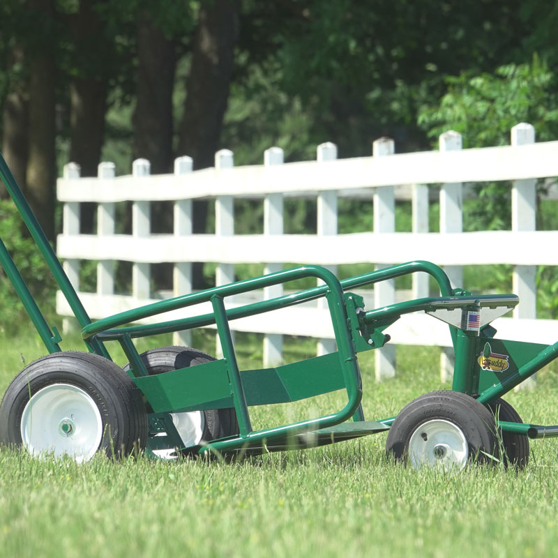 The Landscaper's Buddy tree mover and landscaping utility cart in grass in front of white picket fence.