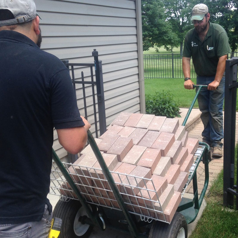 Two men pulling four layers of landscaping brick through a small garden gate on The Landscaper's Buddy and its shelf attachment for hardscapes