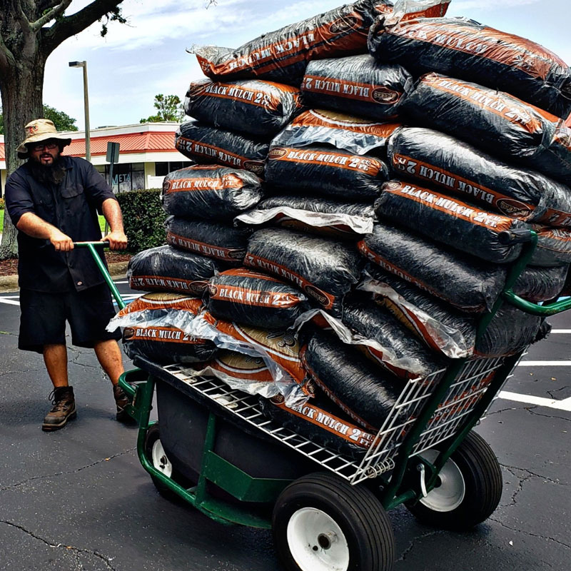 Man hauling over 20 bags of landscaping mulch on on The Landscaper's Buddy with its shelf attachment, a flat cart for up to 2,100 lbs.