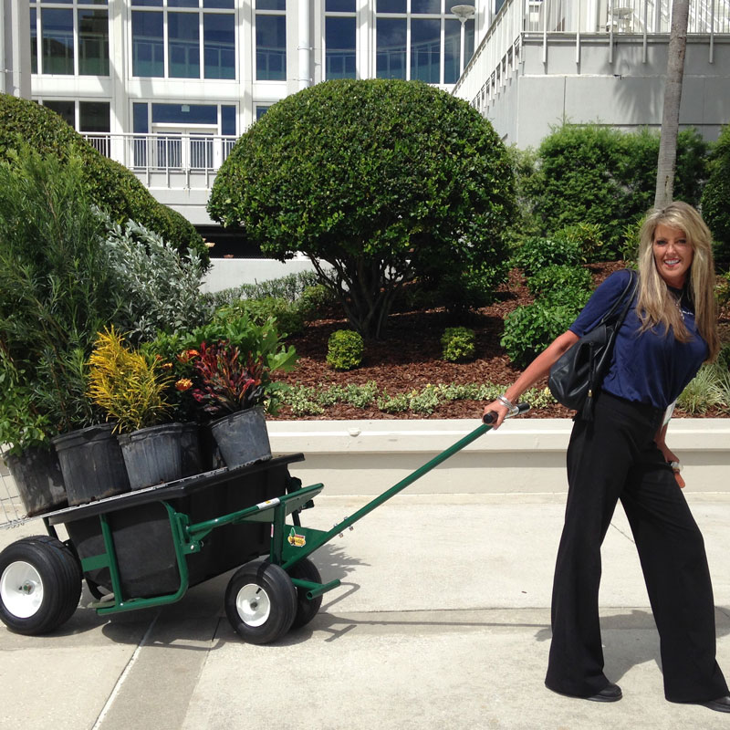Woman smiling while pulling six large potted plants across the street on The Landscaper's Buddy shelf attachment